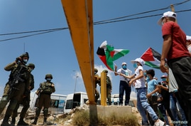 Demonstrators hold Palestinian flags in front of Israeli soldiers during a protest against the United Arab Emirates' deal with…