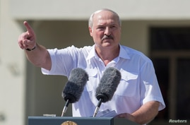 Belarusian President Alexander Lukashenko gestures as he delivers a speech during a rally of his supporters near the Government…