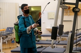 An employee from a disinfection service company wears a protective mask while sanitising sports equipment at the gym of…