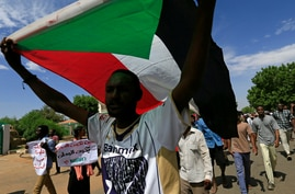 A Sudanese protester carries their national flag as they march in a demonstration to mark the anniversary of a transitional…
