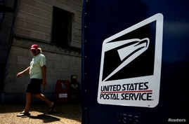 A man walks by a United States Postal Service (USPS) mailbox in downtown Washington D.C., U.S. August 19, 2020. REUTERS/Carlos…