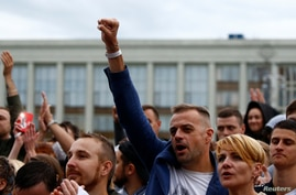 A man raises his fist as he attends an opposition demonstration to protest against presidential election results at the Independence Square in Minsk, Belarus, Aug. 25, 2020.