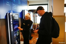 """An employee helps a person buy a ticket inside the Odeon Luxe Leicester Square cinema, on the opening day of the film """"Tenet"""", amid the coronavirus disease (COVID-19) outbreak, in London, Britain, Aug. 26, 2020."""