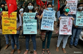 Students wearing protective face masks hold placards as they participate in a protest march demanding postponement of admission…