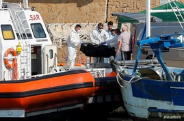 Emergency services carry a body at the dock of Le Castella after a migrant boat caught fire during rescue operations off the…