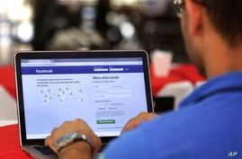 FILE - In this Thursday, Jan. 4, 2018, file photo, a man enters his Facebook page, at a restaurant in Brasilia, Brazil. Federal…