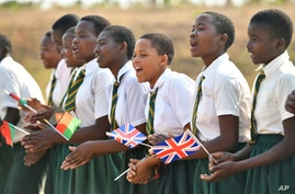 School c hildren sing as they wait for a visit by Britain's Prince Harry, at Nalikule College of Education in Malawi, Sunday…