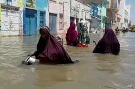 In this image made from video taken Sunday, May 17, 2020, people wade through a flooded street in Beledweyne, central Somalia…