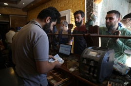People exchange money in the city of Idlib, Syria, Saturday, June 20, 2020. In the northwestern province of Idlib, the last…