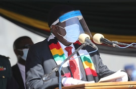 FILE - Zimbabwean President Emmerson Mnangagwa addresses mourners at the burial of Zimbabwean minister Perence Shiri, who died of Covid-19, during his burial in Harare, July, 31, 2020.