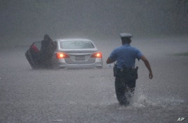 A Philadelphia police officer rushes to help a stranded motorist during Tropical Storm Isaias, Aug. 4, 2020, in Philadelphia.