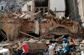 Citizens ride their scooters and motorcycles pass in front of a house that was destroyed in Tuesday's massive explosion in the…