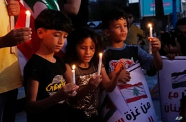 Palestinian children light candles to show their solidarity with the Lebanese people following the explosion in the port of Beirut, at the unknown soldier square in Gaza City, Aug. 6, 2020.