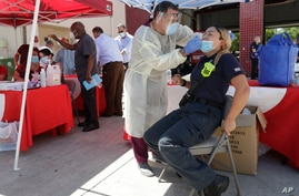Hialeah Fire Department Firefighter-Paramedic Laura Nemoga, right, winces as medical assistant Jesus Vera performs a COVID-19 test, Aug. 6, 2020, at Hialeah Fire Station #1, in Hialeah, Florida.