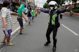 A traffic officer instructs jobless jeepney drivers to practice social distancing as they line up to receive food donations…