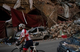 A cyclist rides past destroyed buildings and cars in a neighborhood near the site of last week's explosion that hit the seaport of Beirut, Lebanon, Aug. 11, 2020.