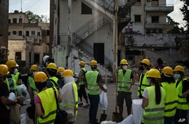 Volunteers from the American University of Beirut gather as they prepare to help remove debris in a neighborhood near the site of last week's explosion that hit the seaport of Beirut, Lebanon, Aug. 13, 2020.