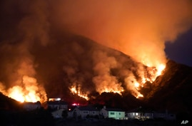 The Ranch Fire burns over a residential area, Aug. 13, 2020, in Azusa, California. Heat wave conditions were making difficult work for fire crews battling brush fires and wildfires across Southern California.
