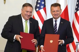 U.S. Secretary of State Mike Pompeo, left, and Poland's Minister of Defence Mariusz Blaszczak pose for the media after signing the US-Poland Enhanced Defence Cooperation Agreement in the Presidential Palace in Warsaw, Poland Aug. 15, 2020.