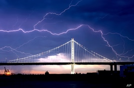 Lightning forks over the San Francisco-Oakland Bay Bridge as a storm passes over Oakland, California, Aug. 16, 2020. Numerous lightning strikes early Sunday sparked brush fires throughout the region.