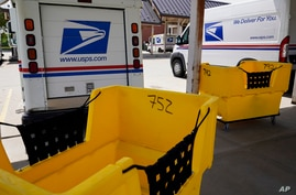 Mail delivery vehicles are parked outside a post office in Boys Town, Neb., Aug. 18, 2020.