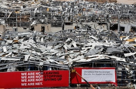 A worker sets banners at the port warehouses that were destroyed by Aug. 4 explosion that hit the seaport of Beirut, Lebanon,…