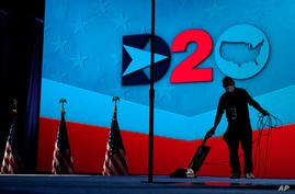 A worker vacuums the stage where Democratic vice presidential candidate Sen. Kamala Harris, D-Calif., will speak on third day…