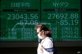 A woman walk in front of an electronic stock board showing Japan's Nikkei 225 and NY Dow indexes at a securities firm in Tokyo, Aug. 20, 2020.