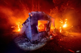 Flames from the LNU Lightning Complex fires consume a home in unincorporated Napa County, Calif., on Wednesday, Aug. 19, 2020…