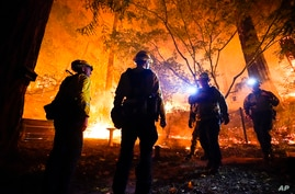 Firefighters make a stand in the backyard of a home in front of the advancing CZU August Lightning Complex Fire, Aug. 21, 2020, in Boulder Creek, California.