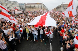 Demonstrators carry a huge historical flag of Belarus as thousands gather for a protest at the Independence square in Minsk, Belarus, Aug. 23, 2020.