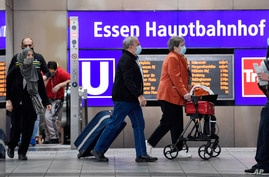 Passengers wear the mandatory face masks at the main train station in Essen, Germany, Monday, Aug. 24, 2020. Police increased…