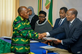 President John Magufuli, left, who seeks a second five-year term, hands over his electoral nomination form to Chairman of the…
