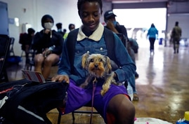 Skyler Brown, 13, holds his dog Chole as they wait to board buses to evacuate Lake Charles, La., Aug. 26, 2020.