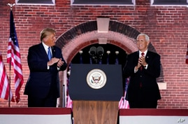 Vice President Mike Pence stands on stage with President Donald Trump after Pence spoke on the third day of the Republican…