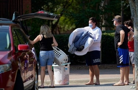 Students and parents begin to move student's belongings out of Bragaw Hall at N.C. State University in Raleigh, N.C., Thursday,…