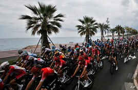 The pack rides along the beach of the Promenade des Anglais during the first stage of the Tour de France cycling race over 156…