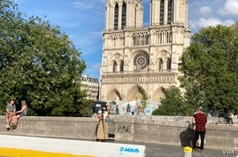 Some enjoy Notre Dame cathedral in Paris, mask-free, despite the city's surging cases. (Lisa Bryant/VOA)