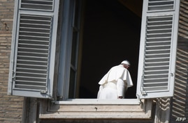 FILE - Pope Francis leaves after turning away from the window of the apostolic palace overlooking an empty Saint Peter's square after delivering his Angelus prayer at the Vatican, March 22, 2020.