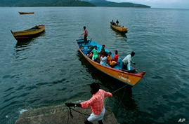 FILE - Fishermen and women return to their homes in Port Blair, in India's Andaman and Nicobar Islands archipelago, Sept. 6, 2007. Authorities say 10 cases have been detected among the Great Andamanese tribe, whose numbers have dwindled to 56.