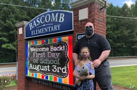 John Barrett and his daughter Autumn pose for photos outside Bascomb Elementary School in Woodstock, Ga., July 23, 2020.