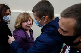 Svetlana Alexievich, the 2015 Nobel literature laureate, second left, looks at a policeman as she arrives for questioning at the Belarusian Investigative Committee in Minsk, Belarus, Aug. 26, 2020.
