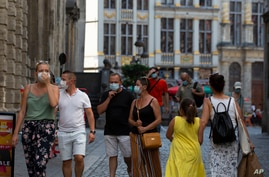 People wear protective face masks as they walk through the Grand Place in the historical center of Brussels, Belgium, Aug. 12, 2020.