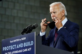 FILE - Democratic presidential candidate former Vice President Joe Biden puts on a face mask after speaking at an event in Lancaster, Pennsylvania, June 25, 2020.