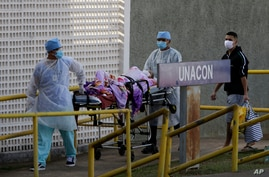 Health workers receive a new patient suspected of COVID-19 arriving at the University Hospital of Brasília, in Brasilia, Brazil, Aug. 5, 2020.