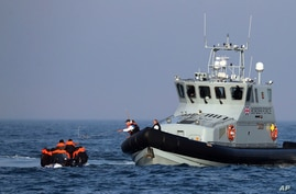A Border Force vessel assists a group of people thought to be migrants on board from their inflatable dinghy in the English Channel.