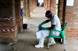 FILE - A health worker in protective gear prepares a disinfectant sprayer at a treatment center in Bikoro, Equateur province, Democratic Republic of Congo, May 13, 2018, during an earlier Ebola outbreak.
