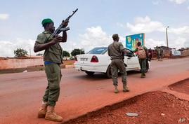 Malian soldiers check a vehicle in the garrison town of Kati, Aug. 18, 2020.
