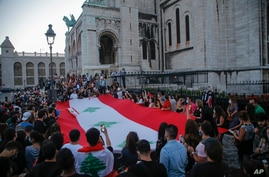 Members of the Lebanese community hold a giant Lebanese flag during a vigil in memory of victims of the deadly blast in Beirut, in front of Sacre Coeur Basilica in Paris, France, Aug. 5, 2020.
