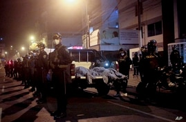 Police officers stand guard outside a disco in Lima, Peru, Aug. 23, 2020.